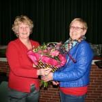 Gea Wolbink (li.) ontving uit handen van Jenny ter Voorde een bos bloemen als dank voor haar inzet als secretaresse van de toneelvereniging EWW.